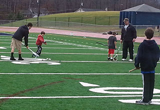 An adult shows a young player how to pick up balls with the lacrosse stick while other players watch.